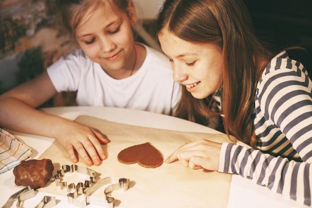 Meninas bonitas na cozinha de casa à mesa cortam biscoitos em forma de coração da massa