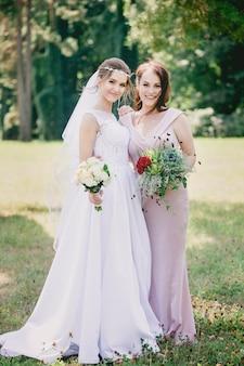 Meninas bonitas noiva e dama de honra com buquês