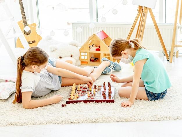 Meninas bonitas que jogam xadrez durante a quarentena