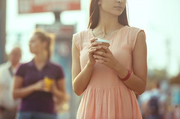 Meninas bonitas, segurando a xícara de café de papel e apreciando o passeio na cidade