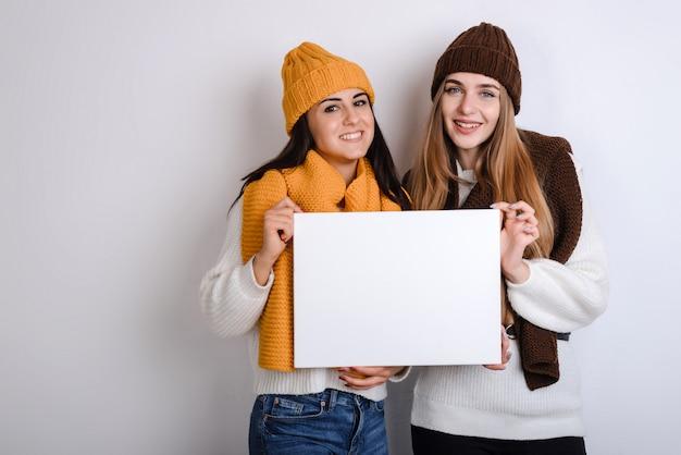 Meninas bonitas, segurando uma folha de papel branco nas mãos, sobre um fundo cinza, isolado