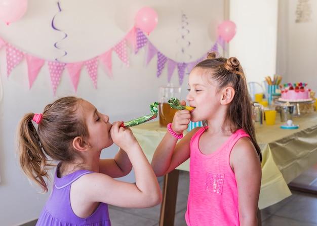 Meninas bonitas soprando chifre de festa aproveitando na festa