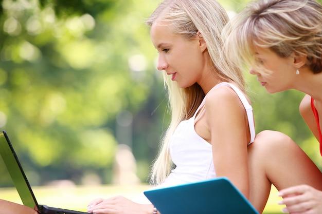 Meninas bonitas usando laptops em um parque