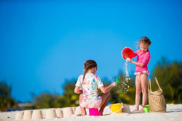 Meninas bonitos brincando com brinquedos de praia durante férias tropicais