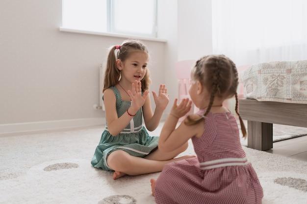 Meninas bonitos despreocupadas jogando adorável em casa