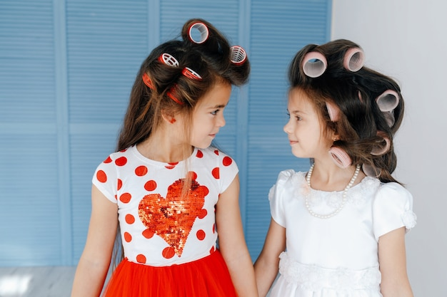 Meninas bonitos elegantes com rolos olhando uns aos outros