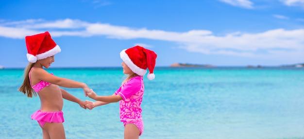 Meninas bonitos em chapéus de papai noel durante as férias de verão