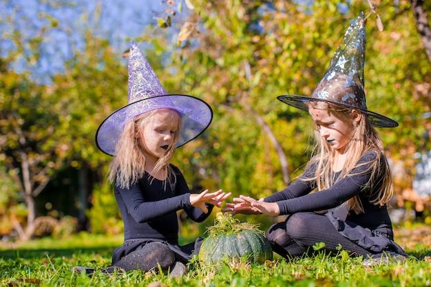 Meninas bonitos pouco lançando um feitiço no halloween em traje de bruxa