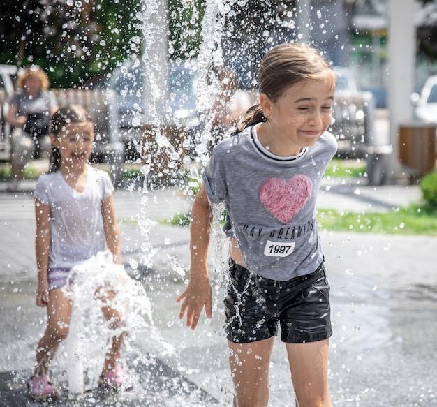 Meninas brincam em uma fonte entre respingos de água.
