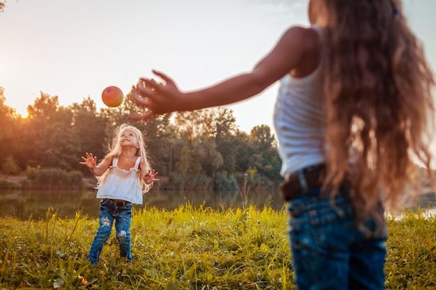 Meninas brincando com bola no parque de verão, crianças se divertindo