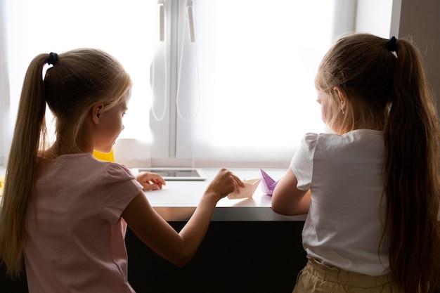 Meninas brincando com papel de origami em casa