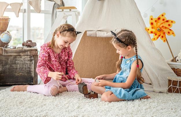 Meninas brincando com uma pequena caixa de tesouro cheia de joias sentadas no chão em uma sala iluminada na cabana