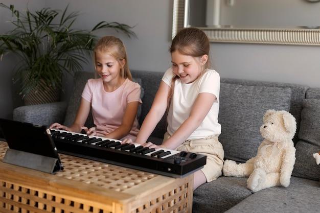 Meninas brincando de teclado em casa