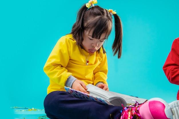 Meninas brincando. jovem de cabelos escuros com transtorno mental empurrando a língua para fora enquanto folheia o livro