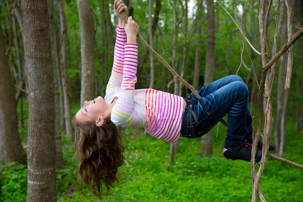 Meninas brincando pendurado em cipós no parque da selva