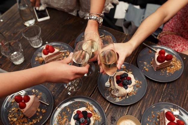 Meninas brinda copos com champanhe no restaurante