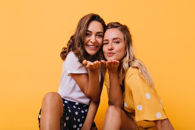 Meninas bronzeadas românticas mandando beijos no ar. amigas alegres expressando amor com um sorriso.