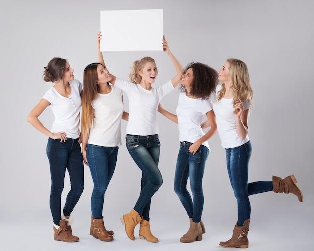 Meninas casuais com quadro branco vazio acima das cabeças