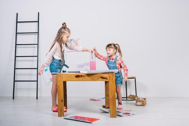 Meninas colocando pincéis em copo de água