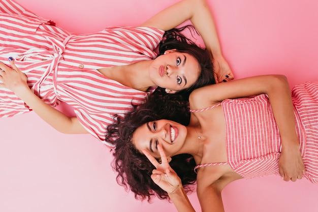 Meninas com aparência de modelo, vestidas com roupas rosa com listras brancas, deitam-se de costas e se contorcem