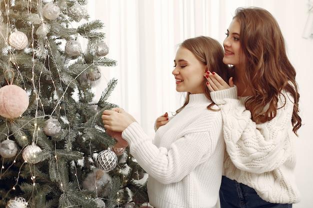 Meninas com brinquedos de natal. mulheres em casa. irmãs estão se preparando para as férias.