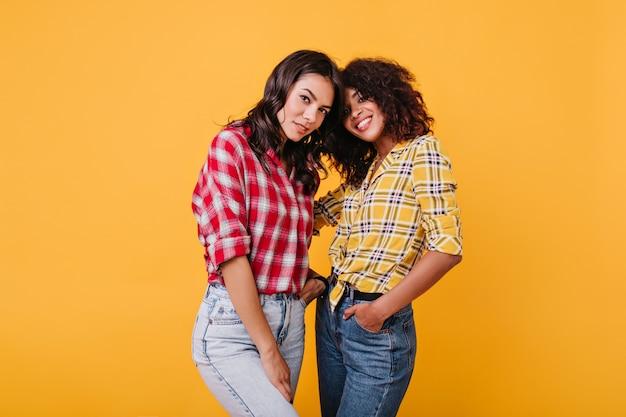 Meninas com cabelo curto escuro olham misteriosamente. senhoras com camisas coloridas se abraçam.