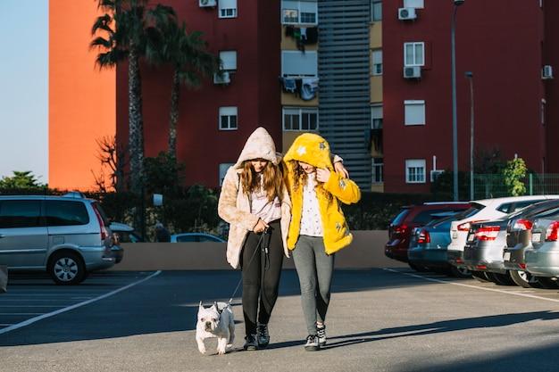 Meninas com cachorro andando no estacionamento