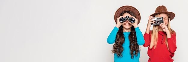 Meninas com câmera e binóculo