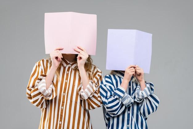Meninas com camisetas listradas de tamanho grande cobrindo o rosto com dobras claras