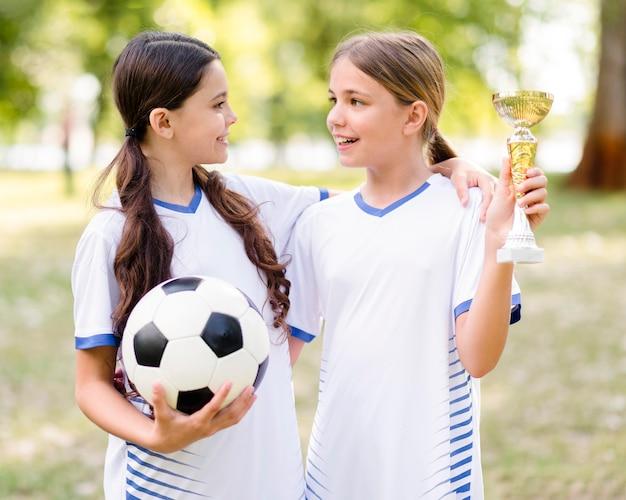 Meninas com equipamento de futebol olhando umas para as outras