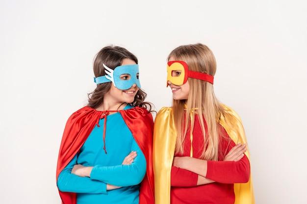 Meninas com fantasia de herói, olhando um ao outro