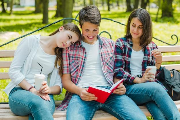 Meninas com homem e livro no banco