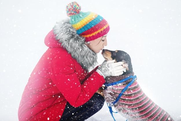 Meninas com jaquetas e chapéus quentes brincam em um parque de inverno com um cachorro passeando