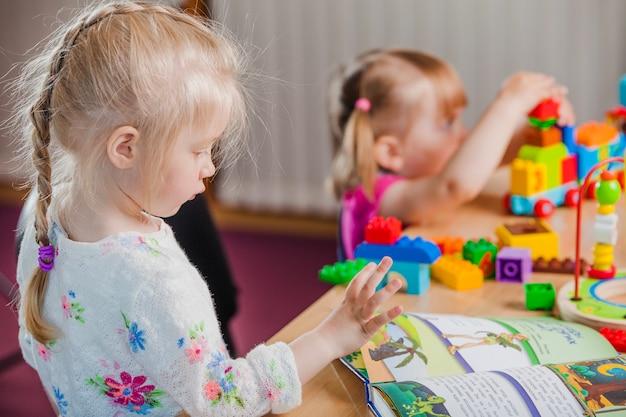 Meninas com livros e brinquedos coloridos