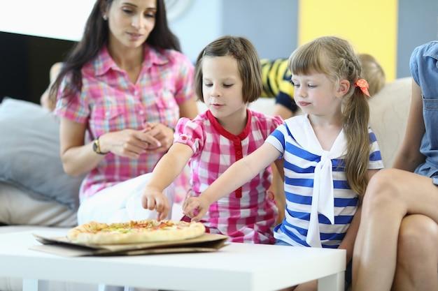 Meninas com mães sentam no sofá e comem fatias de pizza