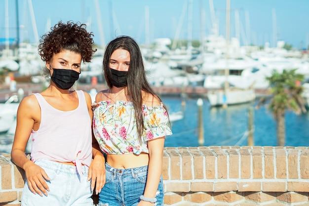 Meninas com máscara facial posando para a câmera em uma praia