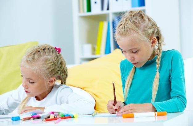 Meninas com muitos lápis de cor sobre a mesa