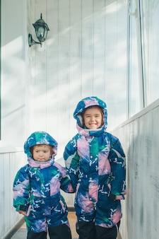 Meninas com o mesmo macacão quente. roupas de inverno para crianças de todas as idades