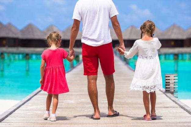 Meninas com o pai no cais de madeira perto de bangalô de água no resort exótico
