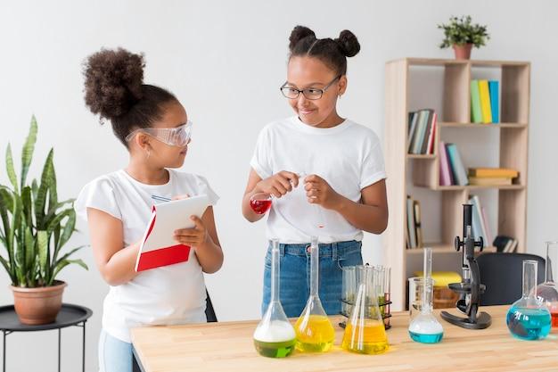 Meninas com óculos de segurança se divertindo com experimentos de química