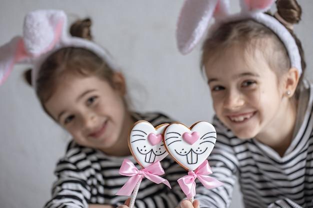 Meninas com orelhas de coelho da páscoa na cabeça estão segurando biscoitos de gengibre em palitos.