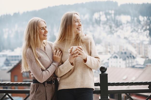 Meninas com roupas leves. café de inverno na varanda. mulheres felizes juntas.