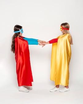 Meninas com traje de heróis de mãos dadas