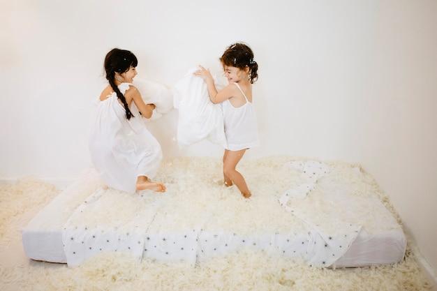 Meninas com travesseiros lutam