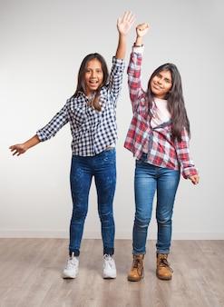 Meninas com um braço levantado