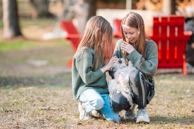 Meninas com um cachorro branco. um filhote de cachorro nas mãos de meninas