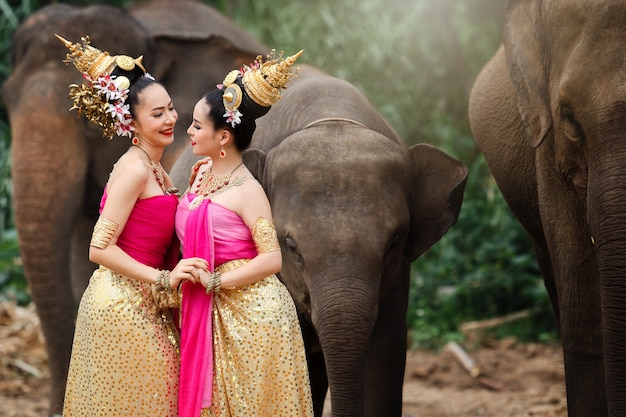 Meninas consideravelmente tailandesas em trajes tailandeses tradicionais com elefantes.
