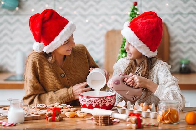 Meninas cozinhando pão de mel de natal. cozinhar e cozinhar com as crianças para o natal em casa.