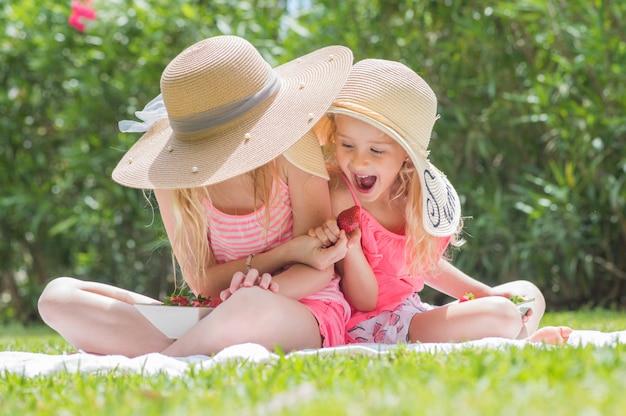 Meninas crianças felizes comendo morangos. diversão no verão