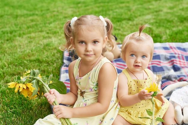 Meninas crianças no parque de verão, irmãs com girassóis em um piquenique